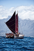 "Voyaging canoe Hokule'a nears Cape Town, with Twelve Apostles (peaks in the distance), South Africa, November 12, 2015; en route between Hout Bay and Cape Town (sailing from Simon's Town). Hokule'a was on a ""Malama Honua"" (Care for the Earth) worldwide voyage to raise awareness about the importance of protecting the world's oceans, considered the greatest environmental challenge of our time."