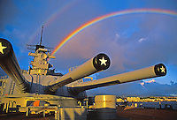 The U.S.S Missouri rests peacefully in Pearl Harbor as a floating museum to WWII naval history.  A colorful hawaiian rainbow shines above the battleship.