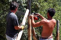 Giardinieri costruiscono la recinzione sui confini un terreno. Gardeners build a border fence on the ground....