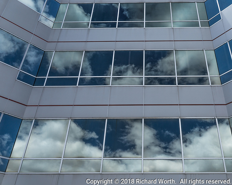 Windows of an urban office building capture the blue and white sky in lines and rectangles.