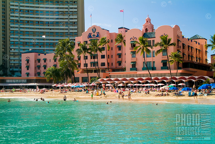 """The classic Royal Hawaiian Hotel, known as """"""""The Pink Palace"""""""", shot in its entirety with people fronting the hotel on the beach and shimmering turquoise water in the foreground."""