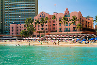 "The classic Royal Hawaiian Hotel, known as """"The Pink Palace"""", shot in its entirety with people fronting the hotel on the beach and shimmering turquoise water in the foreground."