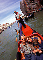 A smiling, retired senior couple enjoys a ride in a traditional gondola in a Venice canal. Venice, Italy.