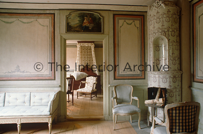 A view from the sitting room furnished with powder blue seating and a tiled stove, into the adjacent bedroom