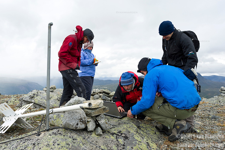Students and their professor use a laptop to record temperatures of the ground and test for permafrost levels in Norway's Jotunheimen National Park. The students are studying climate change.