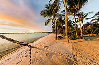 Golden sunset light on a palm tree sand beach and hammock in Bora Bora, romantic honeymoon destination, near Tahiti, French Polynesia, Pacific Ocean