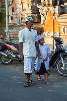 Bali, Indonesia.  Father and Son Walking to the Temple.  Both wear the udeng, the traditional Balinese male head cloth.  Pura Dalem Temple, Dlod Blungbang Village.