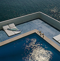 An aerial view of a swimming pool terrace with the calm waters of the Mediterranean below
