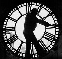 Changing times. It's four months - give or take a day or two - to the vernal equinox and; with any luck; Tony Partington's restoration will go like clockwork. He's shown repairing one of four 7-foot-diameter clockfaces atop the Queen-s Quay Terminal. It's due to reopen this spring - after renovation and additions - as a retail; commercial and residential showplace overlooking Toronto Harbor. The top four floors are to be luxury condominiums; the main floor a glittering mall; with offices on the floors separating tenants from shoppers.<br /> <br /> Photo : Boris Spremo - Toronto Star archives - AQP