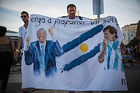 "An Argentine fan displays a banner with the flag of Argentina and figures of Nestor Kirchner and Messi, and the phrase ""I come to propose a dream"". Hundreds of Argentine fans gathered at the Copacabana beach, a day before the debut for Argentina in the World Cup at the legendary Maracana, which would face Bosnia-Herzegovina. Rio de Janeiro, Brazil."