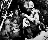 A member of a Marine patrol on Saipan found this family of Japs hiding in a hillside cave.  The mother, four children and a dog, took shelter from the fierce fighting in that area.  June 21, 1944. Cpl. Angus Robertson. (Marine Corps)<br /> Exact Date Shot Unknown<br /> NARA FILE #:  127-GR-113-83266<br /> WAR & CONFLICT BOOK #:  1267