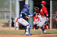 Los Angeles Dodgers catcher Julian Leon (43) waits for a throw as Mitch Trees (33) scores a run during an Instructional League game against the Cincinnati Reds on October 11, 2014 at Goodyear Training Complex in Goodyear, Arizona.  (Mike Janes/Four Seam Images)