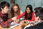Education high school group of students in classroom working on problem together and discussing it