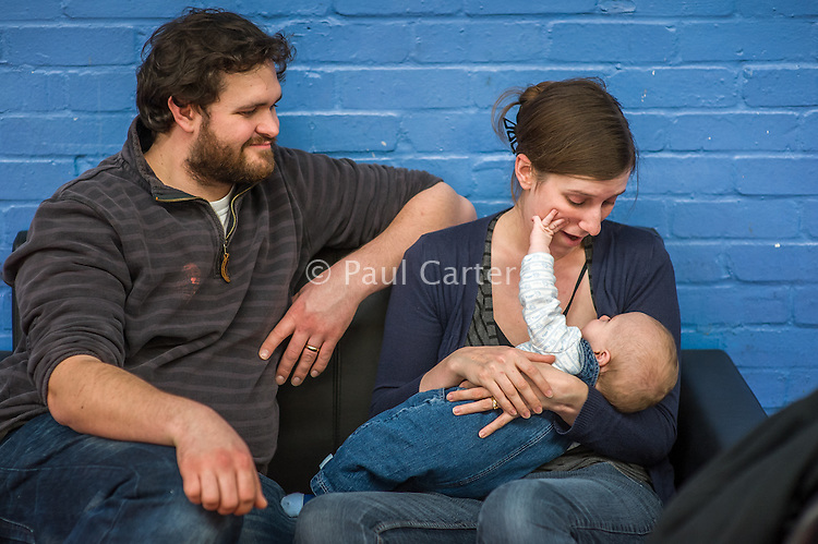 A mother breastfeeds her 5 month old son at a play centre. The baby plays with the mother's face.<br /> <br /> Hampshire, England, UK<br /> 21/03/2016<br /> <br /> © Paul Carter / wdiip.co.uk