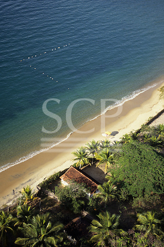 Ilha Grande, Brazil. Aerial view of house on the sandy beach surrounded by palm trees with line of marker floats.