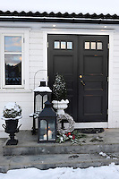 Outside the front door festive lanterns protect fragile candles.  Cast iron urns, spruce branches, christmas apples and a wreath add to the Christmas feel