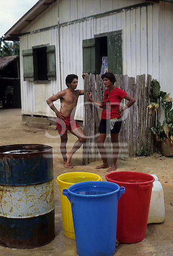 Belterra, Brazil. Man and woman outside a wooden house with plastic water containers in bright blue, yellow and red dustbins; oil drum. Para State.