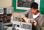 Teenagers workplace male intern working with computer parts salvaging and repairing horizontal