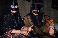 Muscat, Oman, Arabian Peninsula, Middle East - Masked Omani Women.  Note the henna design on the hand of the woman on the left.