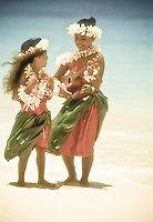 Young hula girls on beach with plumeria leis playing the ukulele