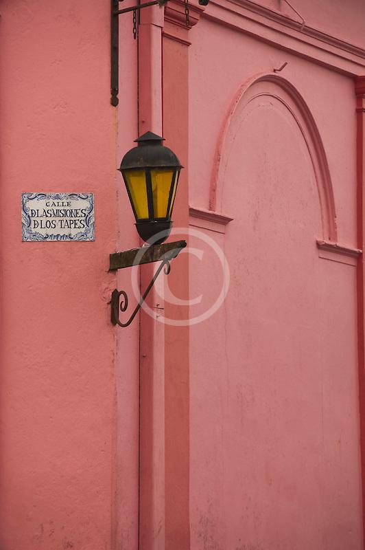 Uruguay, Colonia del Sacramento, Single lamp and sign on orange wall, Historic District