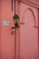 Uruguay, Colonia del Sacramento, Single lamp and sign on orange wall, Historic District
