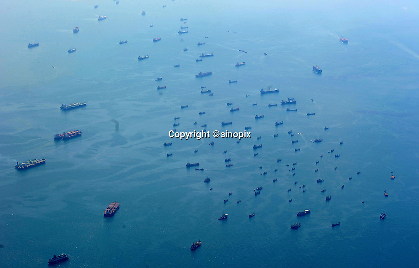 Container ships are tied together several kilometers out to see off the coast of Malaysia. There are hundreds of container ships and oil tankers moored in a 30 km stretch in international waters where it is cheap to moor the boats.