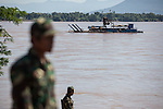 20 October 2013, Pakse, Laos:  A Lao Government soldier stands on the crash site with a recovery barge sifting the Sedon River for wreckage  following a crash of a Lao Airlines plane into the river at Pakse, Laos. The aircraft crashed into the Mekong River tributary on approach to Pakse airport from Vientiane in severe weather killing all 44 passengers and 5 crew on board. Rescue workers are still dragging the fast flowing river for further remains and the main body of the plane.  Picture by Graham Crouch
