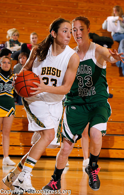 SPEARFISH, SD - JANUARY 4, 2013:  Bailey Kusser #23 of Black Hills State looks past Adams State defender Deanna Reich #33 during their Rocky Mountain Athletic Conference Basketball game Friday at the Young Center in Spearfish, S.D.  (Photo by Richard Carlson/dakotapress.org)