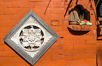Jimbaran, Bali, Indonesia.  Offerings (Canang) in a Wall Recess Adjacent to Entrance to a Restaurant.  Lotus Flower Decoration.