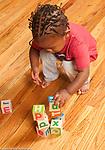 17 month old toddler boy stacking wooden alphabet blocks