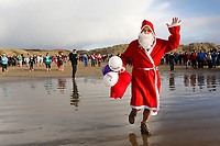 Pictured: A man in Santa clothes take to the sea. Tuesday 26 December 2017<br /> Re: Hundreds took part in this year's Boxing Day Walrus Dip which see people in fancy dress taking to the sea at Cefn Sidan beach in Pembrey Country Park, west Wales, UK.