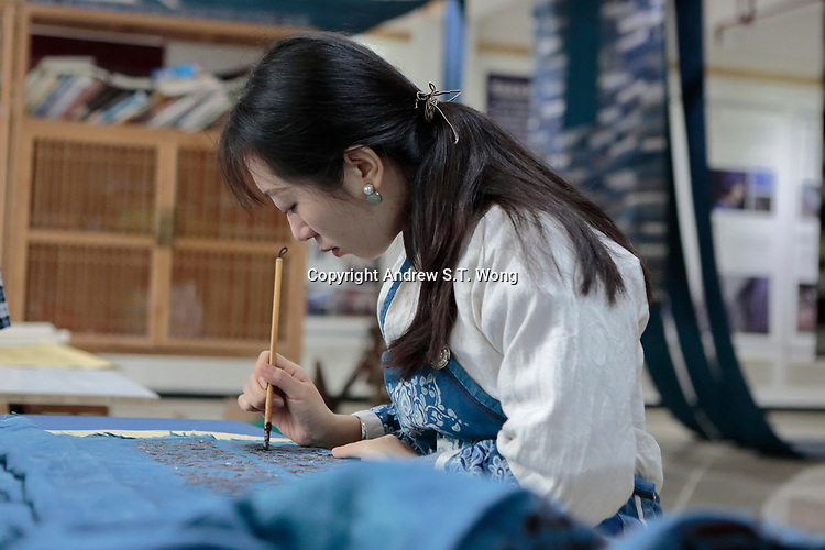 A Bouyei woman draws traditional patterns at ethnic fashion designer Wei Xianglong's studio in Duyu, Guizhou Province, 2018.