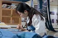 A Bouyei woman draws traditional patterns at ethnic fashion designer Wei Xianglong's studio in Duyu, Guizhou Province, 2018.
