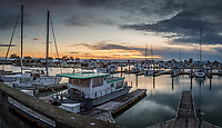 Sailboats, house boats and empty boat slips - sunset at the San Leandro Marina on a winter evening. A multi-image panoramic composition.