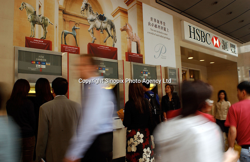 People take money from service tills (ATM) at a  branch of HSBC in Hong Kong. HSBC is Hong Kong and the world's largest bank..