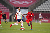 KASHIMA, JAPAN - AUGUST 2: Becky Sauerbrunn #4 of the United States kicks the ball in front of Nichelle Prince #15 of Canada during a game between Canada and USWNT at Kashima Soccer Stadium on August 2, 2021 in Kashima, Japan.