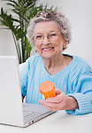Portrait of senior woman holding pill bottle and using laptop