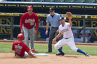 Memphis manager Pop Warner #57 and PCL umpire Jeff Morrow watch the play as Round Rock Express third baseman Adam Rosales #9 catches a throw from the outfield as Memphis Redbirds base runner Scott Moore #12 slides safely into third base during the Pacific Coast League baseball game against the on April 27, 2014 at the Dell Diamond in Round Rock, Texas.  The Express defeated the Redbirds 6-2. (Andrew Woolley/Four Seam Images)