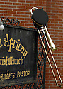 A cap and trombone rest on the Fifth African Baptist Church sign as hundreds of musicians and mourners gathered for the jazz funeral for Dinerral Shavers, 25, who died from a gunshot to the back of his head in New Orleans, Sat., Jan. 6, 2007. Shavers was the snare drummer for the Hot 8 Brass Band and the music teacher at L.E. Rabouin High School, where he had recently begun the school's first-ever marching band. He was killed by a teen who was trying to shoot his stepson. ..(AP Photo/Cheryl Gerber).