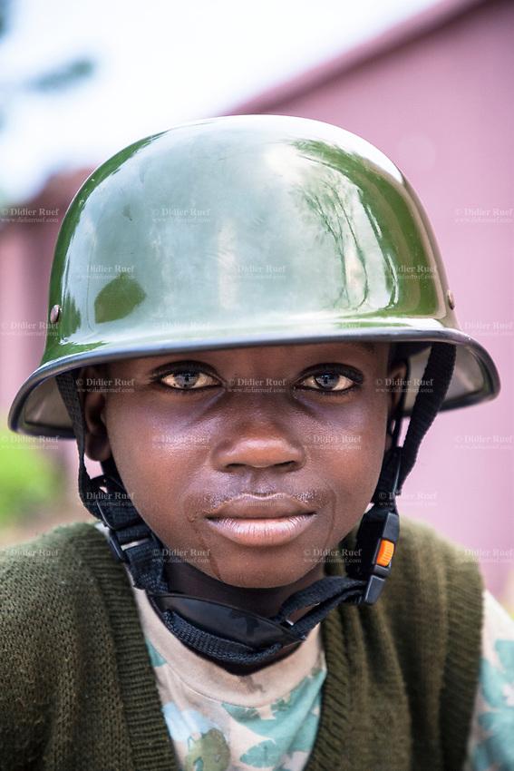 Nigeria. Enugu State. Owo. Outside Saint Mary's Catholic Parish. A young boy with a green military helmet. Portrait. 9.07.19 © 2019 Didier Ruef