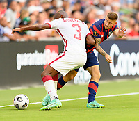 AUSTIN, TX - JULY 29: Abdelkarim Hassan #3 of Qatar and Paul Arriola #7 of the United States battle for control of the ball during a game between Qatar and USMNT at Q2 Stadium on July 29, 2021 in Austin, Texas.