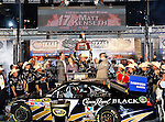 Matt Kenseth, driver of the (17) Crown Royal Black Ford, hoists the trophy up overhead as Eddie Gossage Jr. congratulates him after winning the Samsung Mobile 500 Sprint Cup race at Texas Motor Speedway in Fort Worth,Texas.
