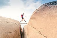 Happy female hiker jumping across a gap between boulders along the Sotoleden trail, West Sweden, Sweden - Västsverige, Sverige