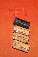 Four corks in a row from the Chakana Bodega Winery three natural cork and one black plastic synthetic cork all with the text wine from the Andes, on top of a menu from the restaurant with the name of the restaurant red on it. The Restaurant Red at the Hotel Madero Sofitel in Puerto Madero, Buenos Aires Argentina, South America