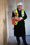 © Joel Goodman - 07973 332324 .  04/02/2014 . Manchester , UK . ED BALLS with a nail gun . Ed Balls , MP for Morley and Outwood and Shadow Chancellor of the Exchequer the Labour Party , joins Labour candidate Mike Kane on the campaign trail ahead of the Wythenshawe and Sale East by-election , following the death of MP Paul Goggins . They visit apprentices at the Leybrook Road building site in Wythenshawe where apprentice builders work on bungalows built for affordable rent . Photo credit : Joel Goodman