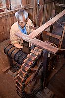 Myanmar, Burma.  Burmese Man of Intha Ethnic Group Spinning Fiber from Lotus Stems in Preparation for Weaving.  Inle Lake, Shan State.