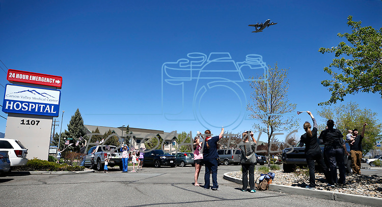 """Dozens of workers and residents watch as three C-130s from the Nevada Air National Guard 152nd Airlift Wing, also known as the """"High Rollers"""", fly over Carson Valley Medical Center, in Gardnerville, Nev., on Tuesday, April 28, 2020. The flyover passed medical facilities around the region to honor first responders battling COVID-19. <br /> Photo by Cathleen Allison"""
