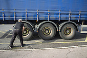 HGV lorry driver checks tyres on a London street