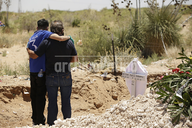 Relatives  of a  Covid 19 pandemic victim in the cementery of  Ciudad Juarez, on the Mexican border with the USA. Amidst the never ending violence of this city, corona virus is taking a high death toll.